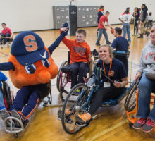 4 people and Otto in wheelchairs on a basketball court.